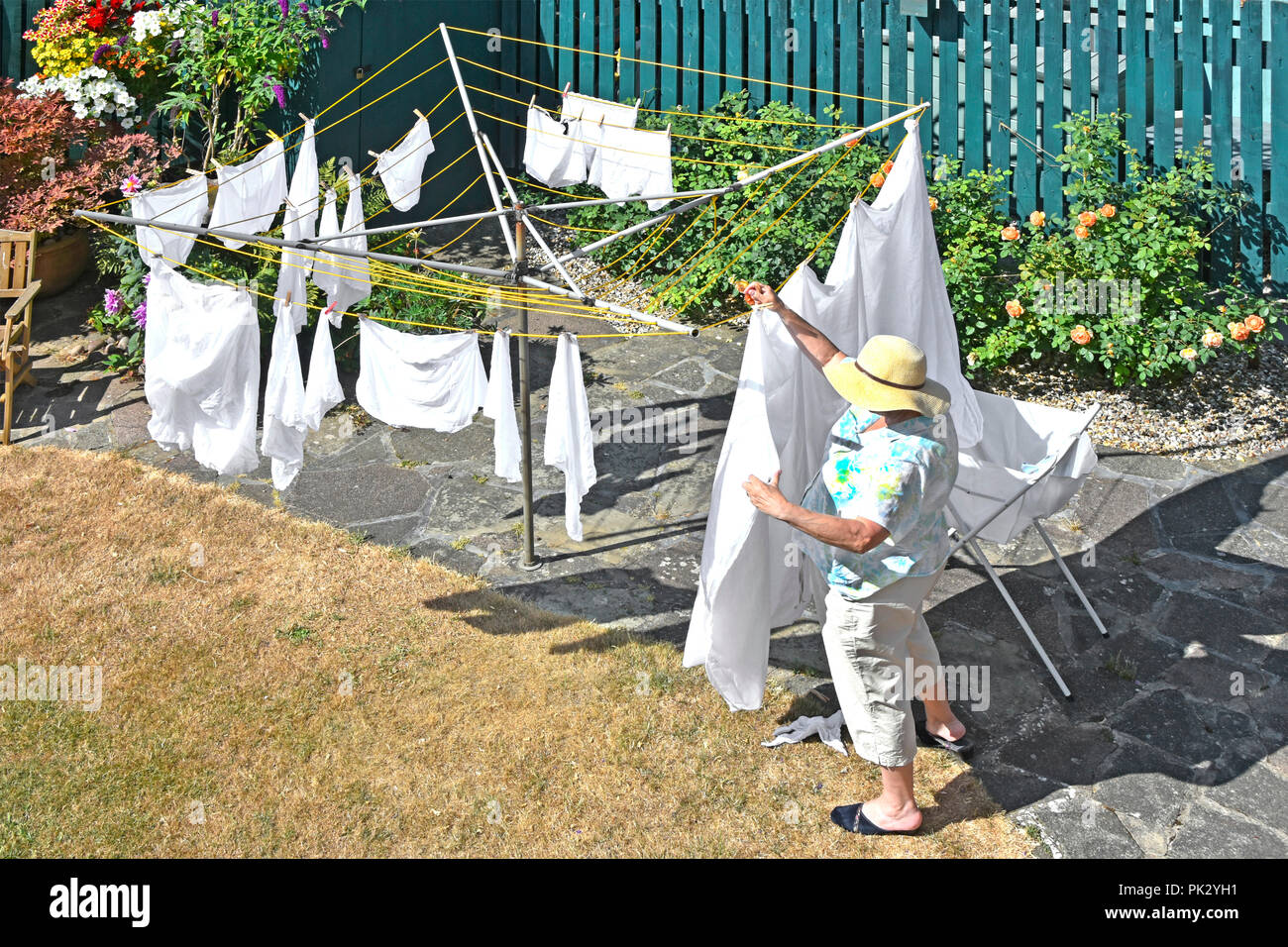 Hot 2018 summer looking down on parched dry back garden lawn & mature senior woman wearing sun hat hanging washing on rotary clothes line England UK - Stock Image
