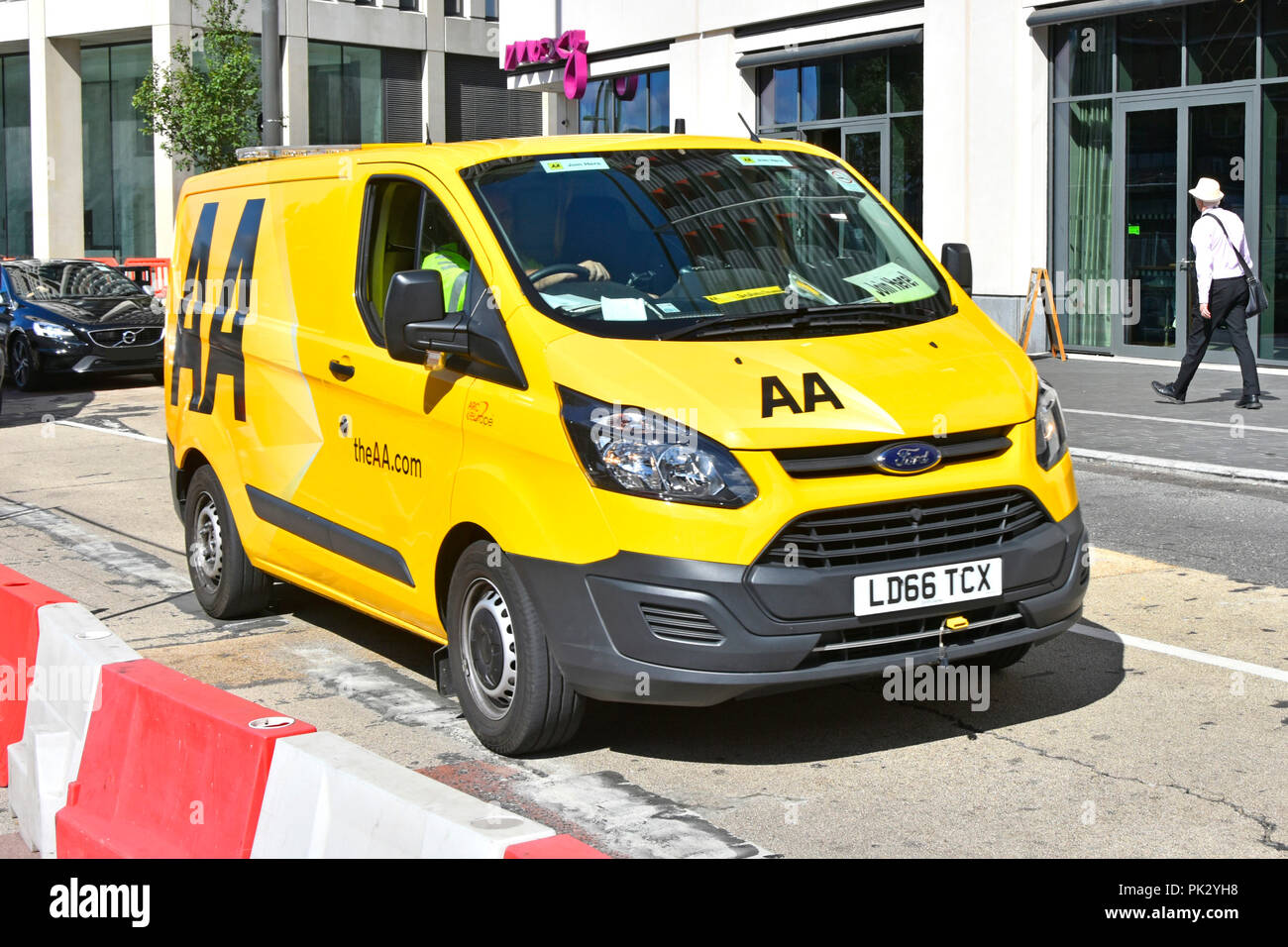 e7fb59602f Ford Transit van   driver with AA logo on yellow breakdown van driving  along town centre