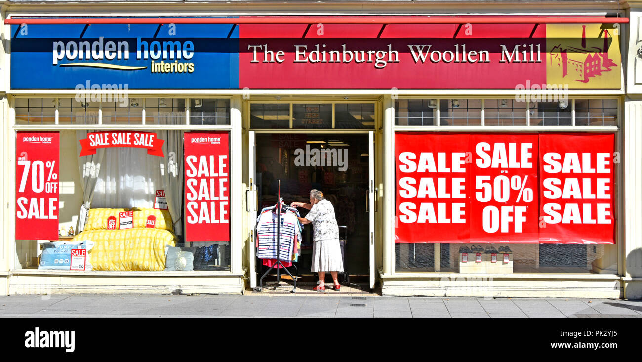 Old lady shopping at clothes rail in entrance Edinburgh Wool Mill high street retail clothing store sale posters shop front window Brentwood Essex UK - Stock Image