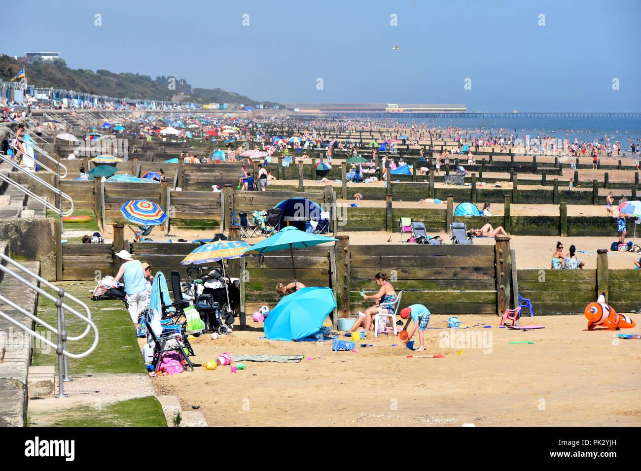 2018 hot weather summer crowds of holiday people on Essex seaside sand coast family beach for safe play & sunbathing Frinton on Sea resort England UK Stock Photo