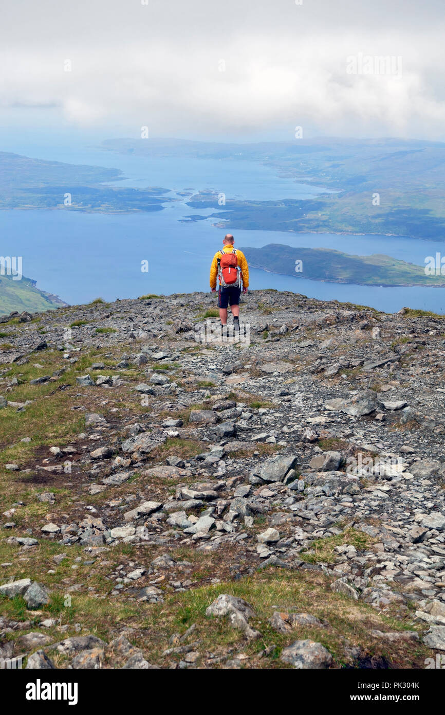 Walker descending Ben More on Mull with views of Loch Na Keal with the island of Eorsa and beyond the narrows between Ulva on the left and Mull Stock Photo