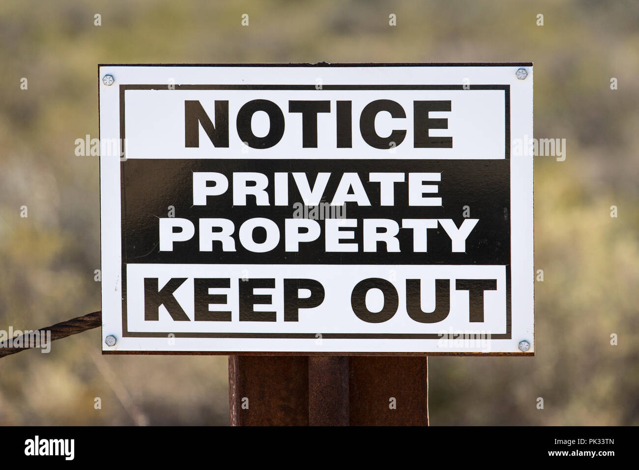 Weathered generic private property keep out sign on rusty metal fence post. - Stock Image
