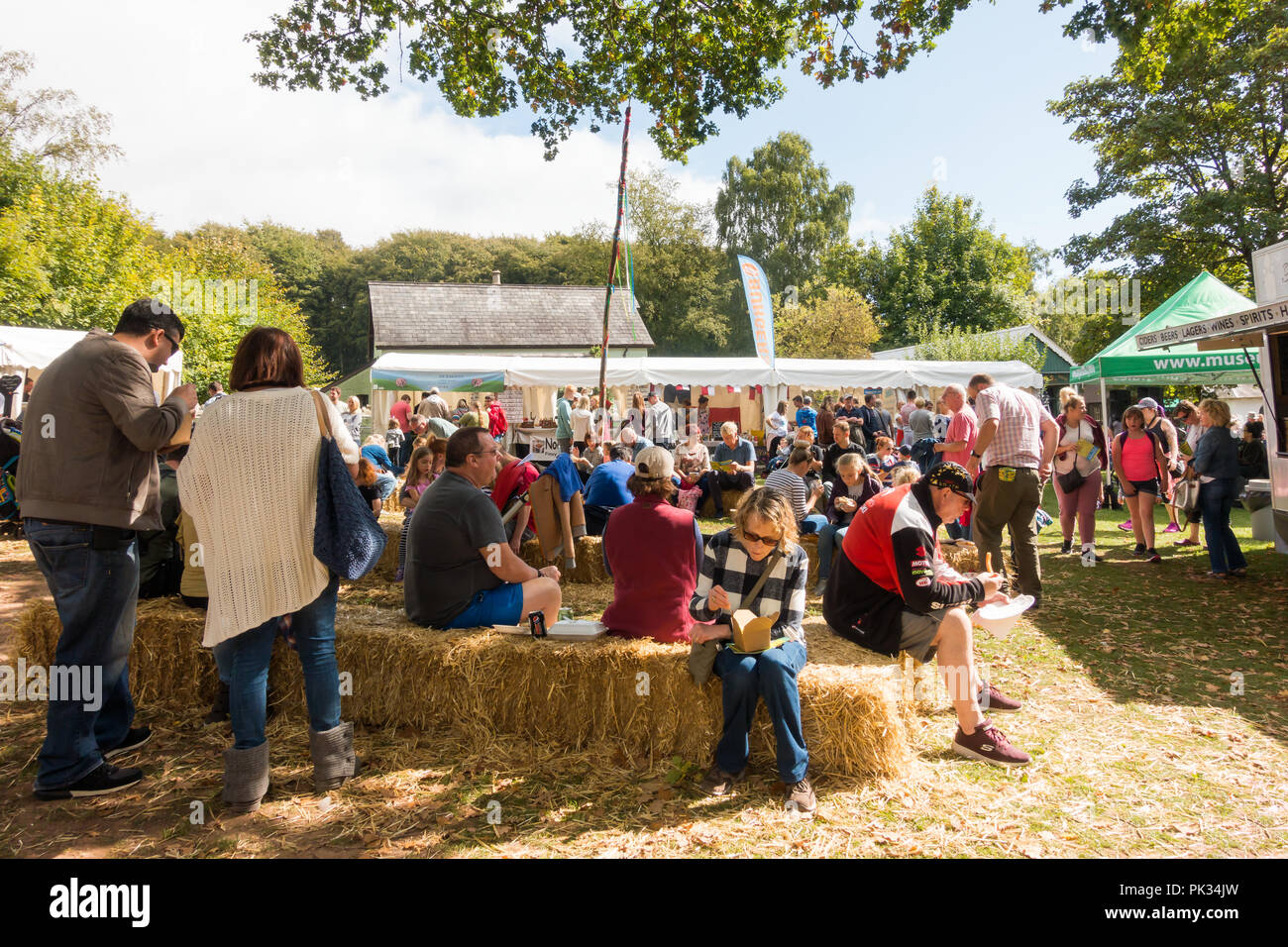 St Fagans, United Kingdom -  July 14, 2017: People sit eating on hay at the Food Festival in St Fagans, Cardiff, Wales - Stock Image