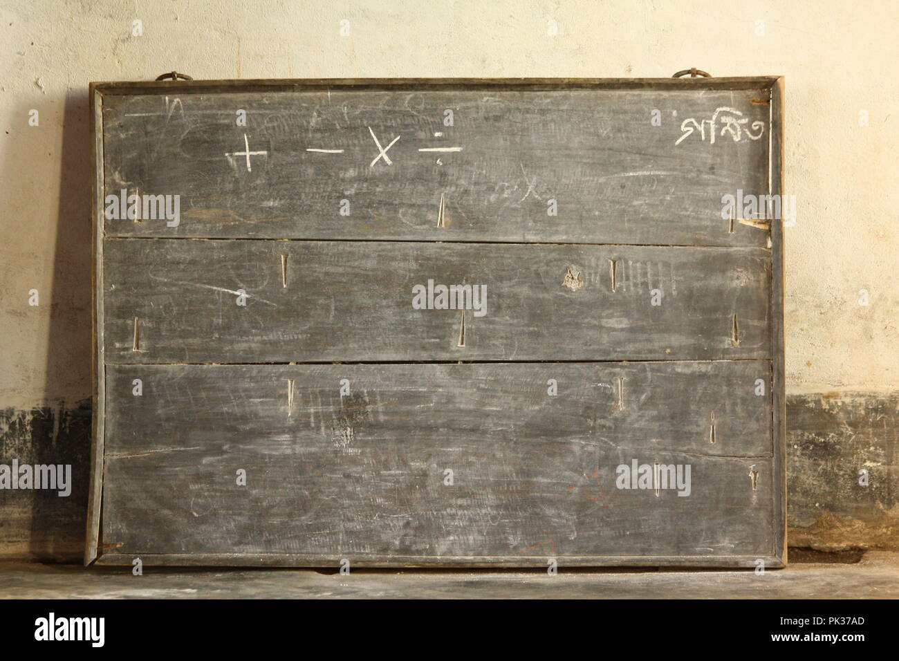 Old blackboard in a developing country standing on the floor of a rural school building. - Stock Image