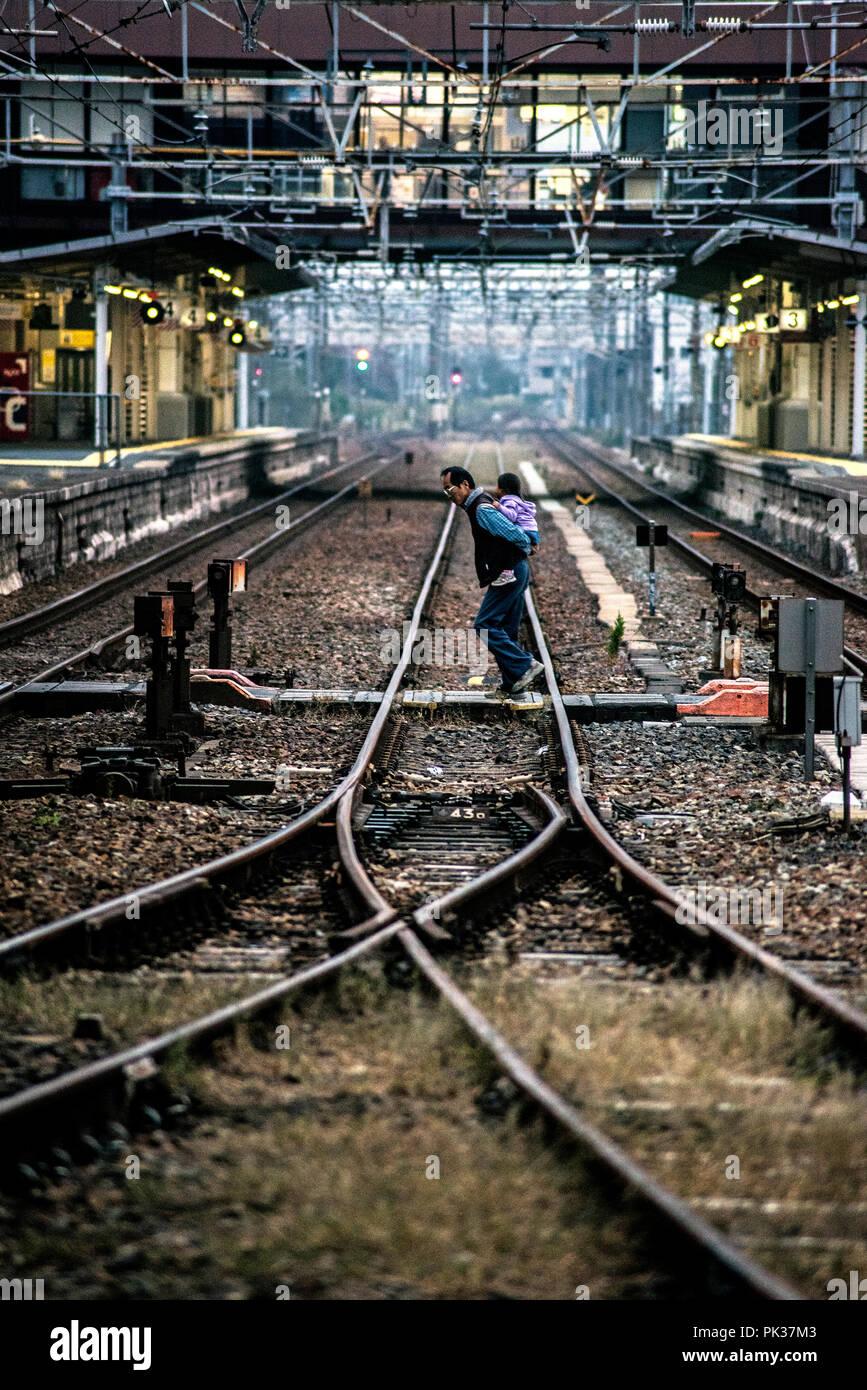 Shin-Kurashiki Station, Tamashima, Japan - November 18, 2015: A Japanese father crosses the railway with his child in his arms, on his back. Stock Photo