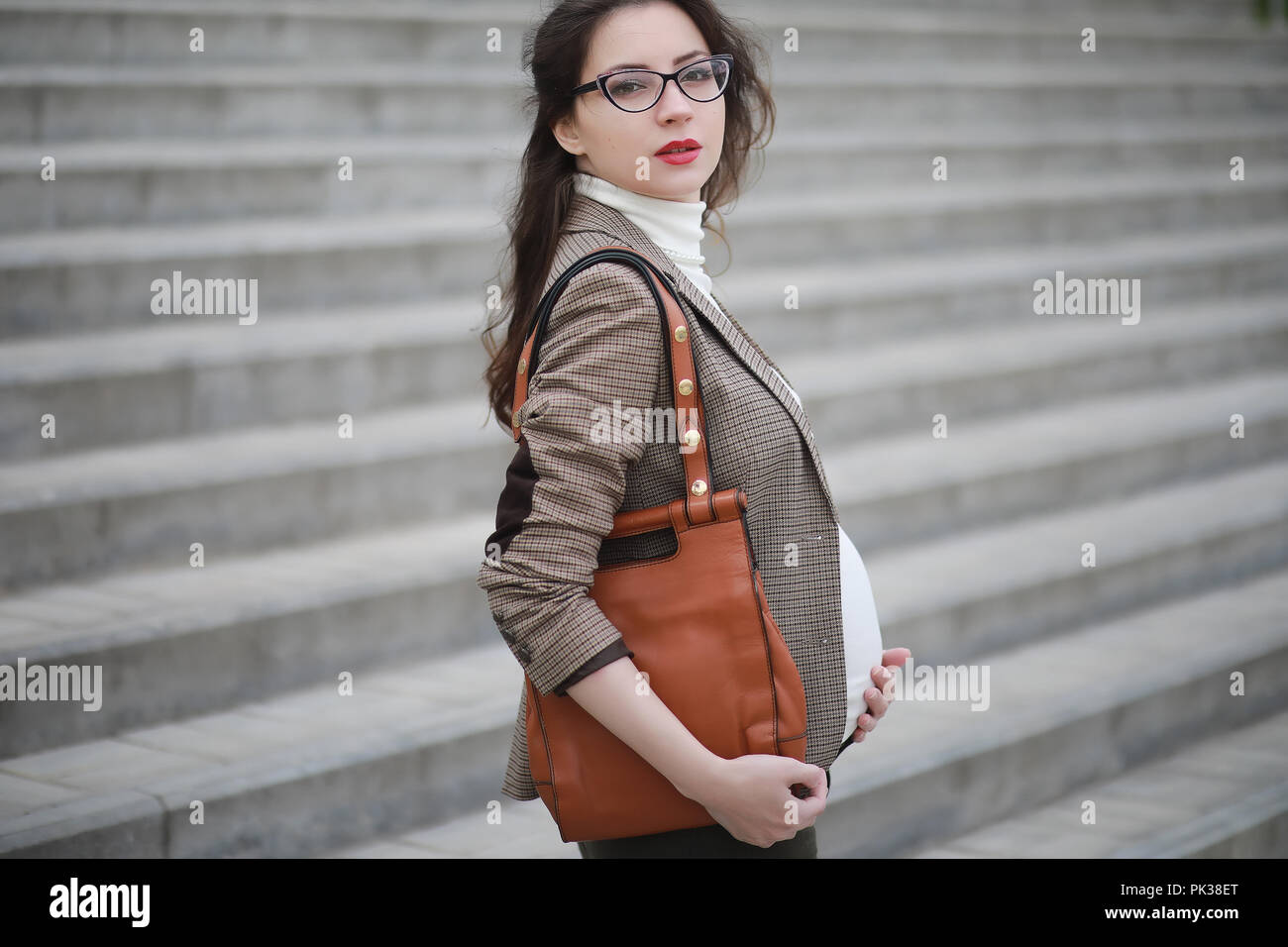 Pregnant woman talking on the phone in the street - Stock Image