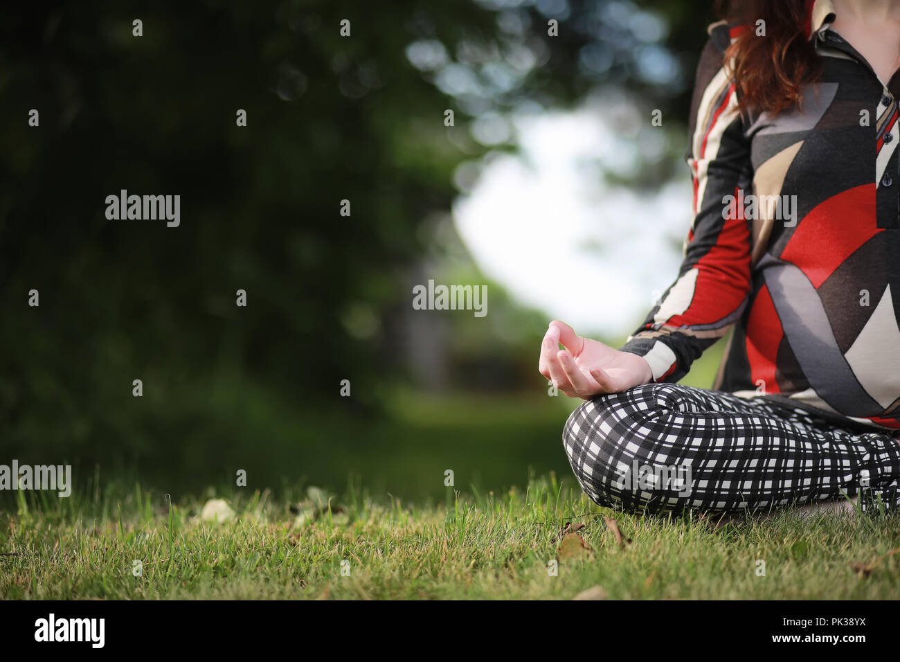 Pregnant woman doing yoga exercise in nature - Stock Image