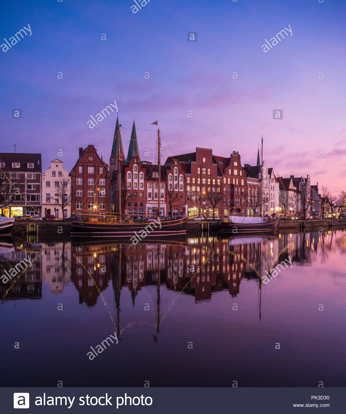 View over the old town and the harbour of Lübeck after sunset - Stock Image