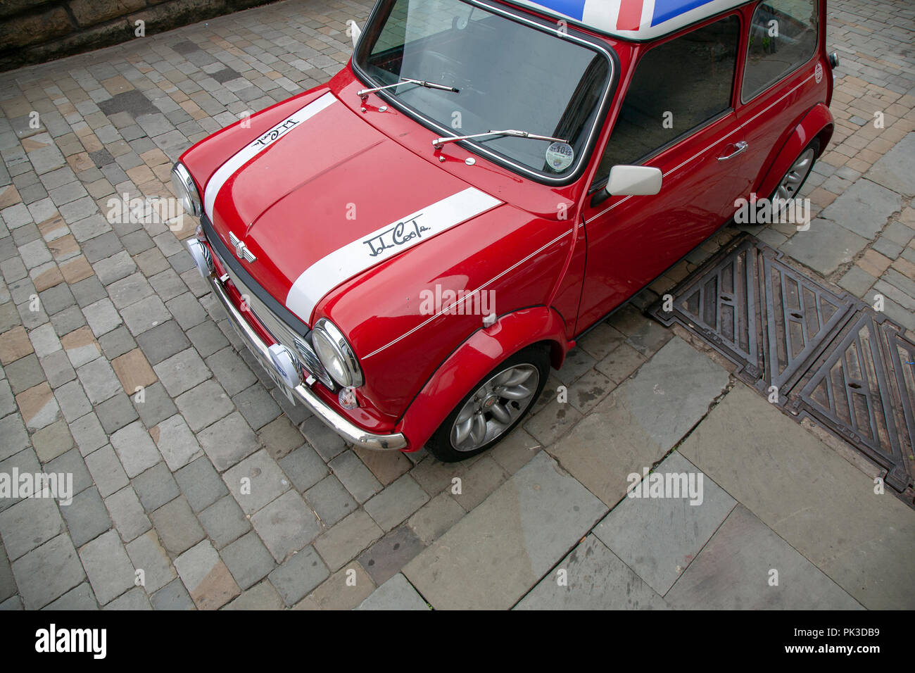 A Red Mini Cooper wth a Union Jack Roof by John Cooper version of the mini parked on a cobbled street in Huddersfield - Stock Image
