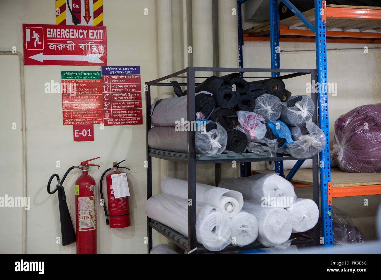 Fire extinguishers and emergency exit sign inside a garment factory in Bangladesh. - Stock Image