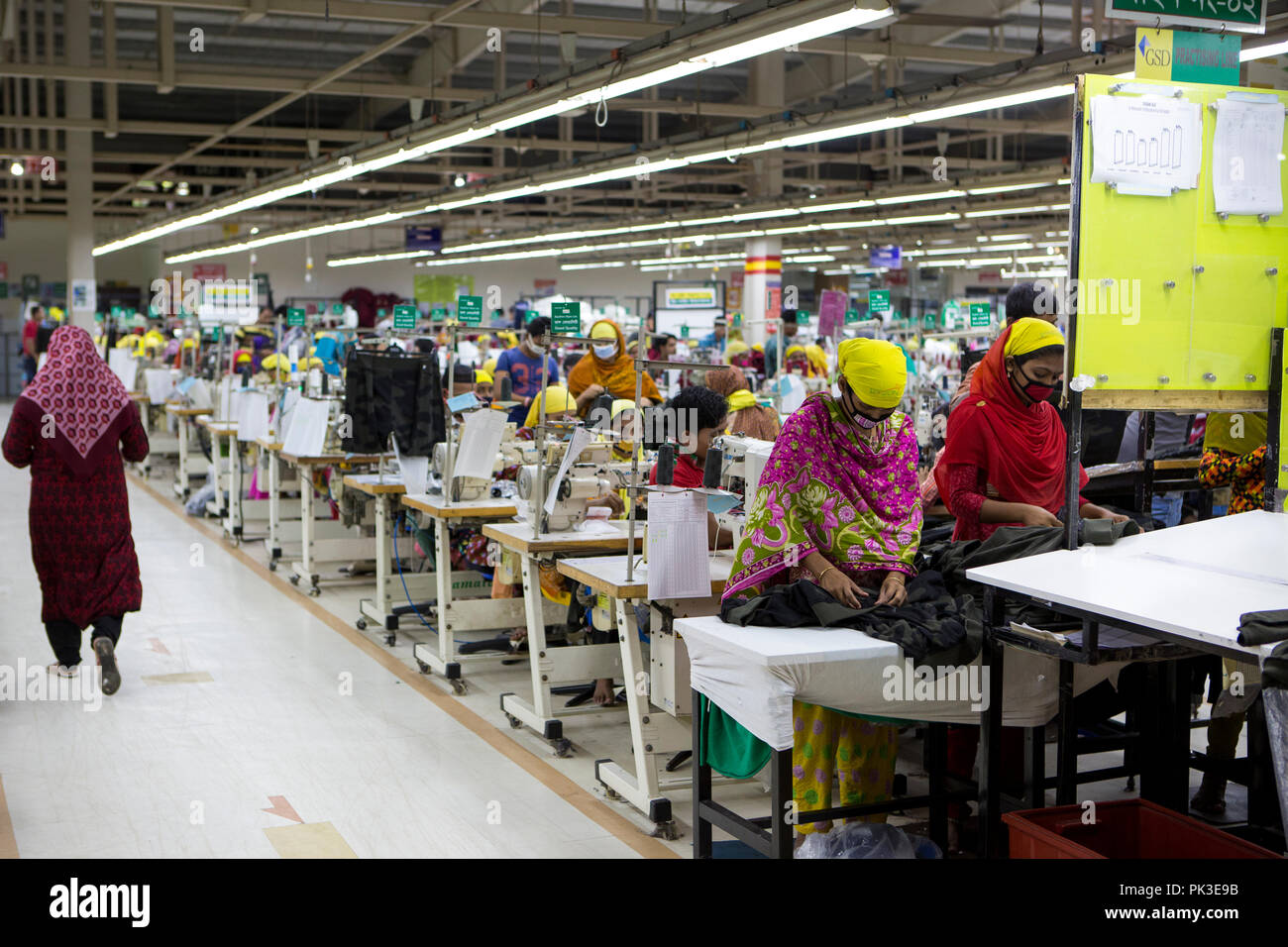 Garment workers at work on sewing machines inside a garment factory in Bangladesh. - Stock Image