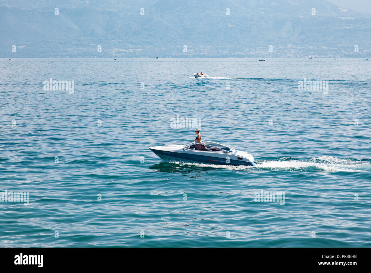 Couple on speed boat on Lake Leman (Geneva Lake) on beautiful sunny summer day - Stock Image