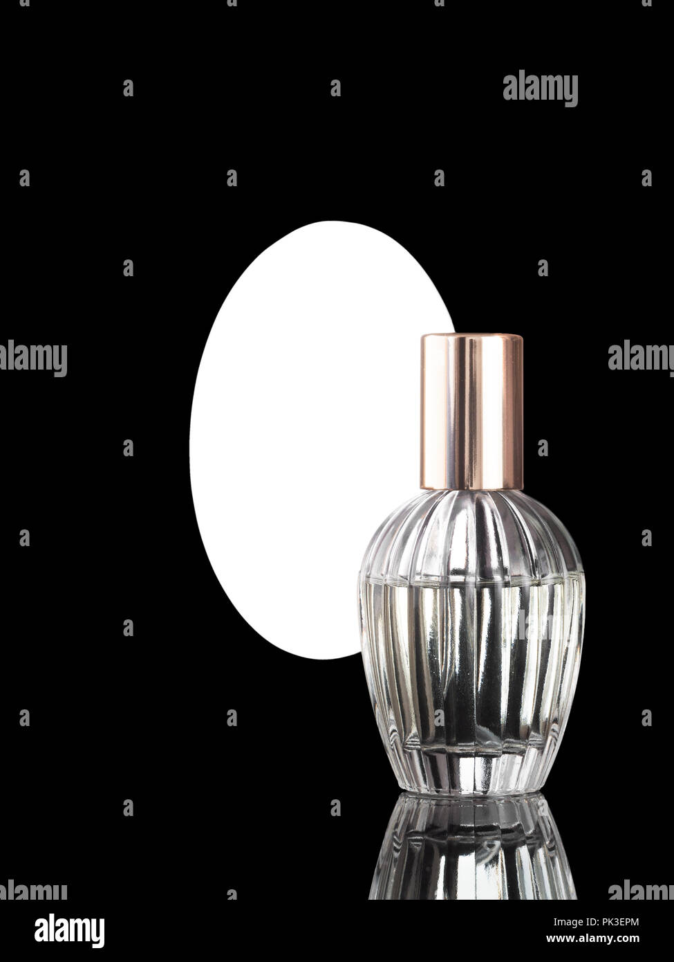 Elegant perfume bottle on shiny black background with mirror behind and copyspace. - Stock Image