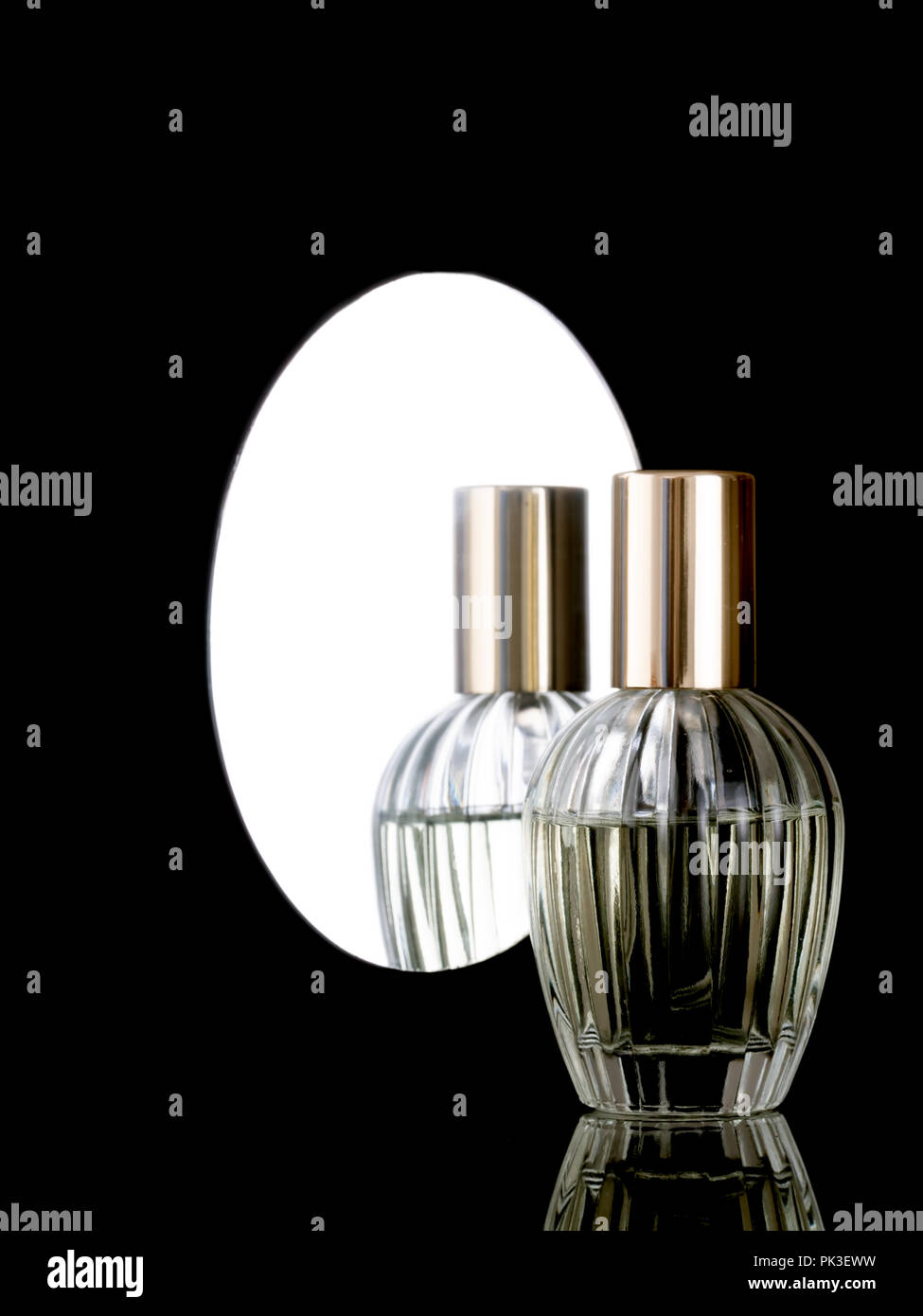 Elegant clear glass perfume bottle on a shiny black background with reflection also in mirror behind. With copyspace. - Stock Image