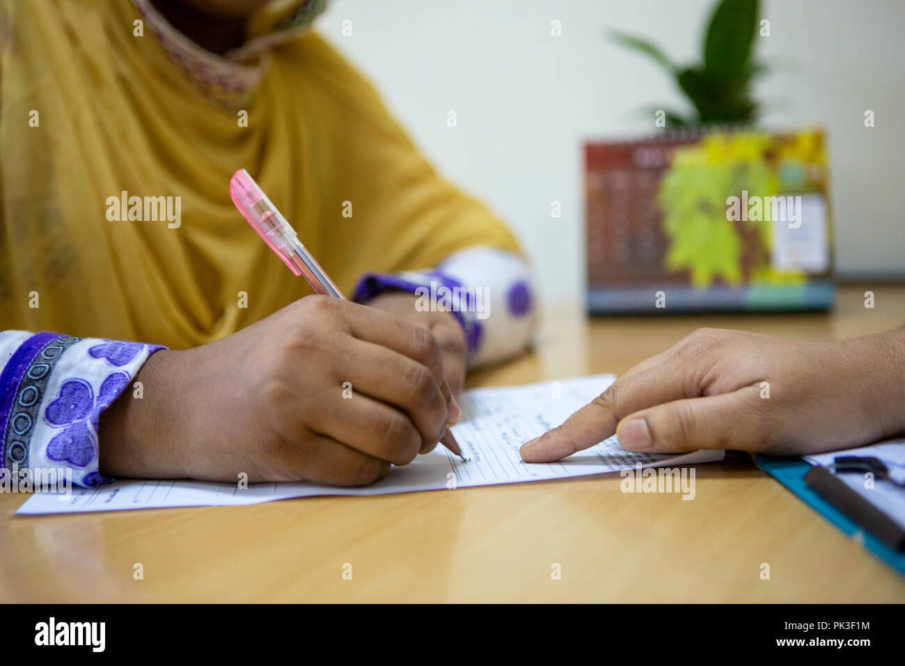 A female garment worker meeting with her manager in garment factory in Bangladesh. - Stock Image