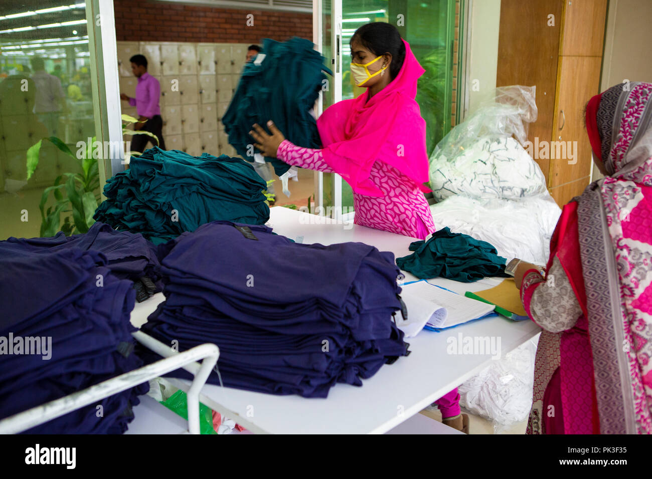 A garment worker sorts through piles of clothes inside a garment factory in Bangladesh. - Stock Image