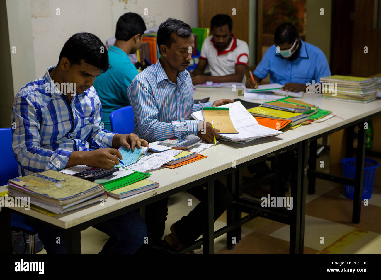 Stock check, accounting and processing orders inside a garment factory in Bangladesh. - Stock Image