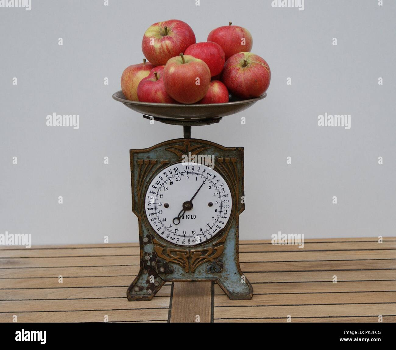 Closeup of a nostalgic kitchen scale with apples on the scales pan - Stock Image