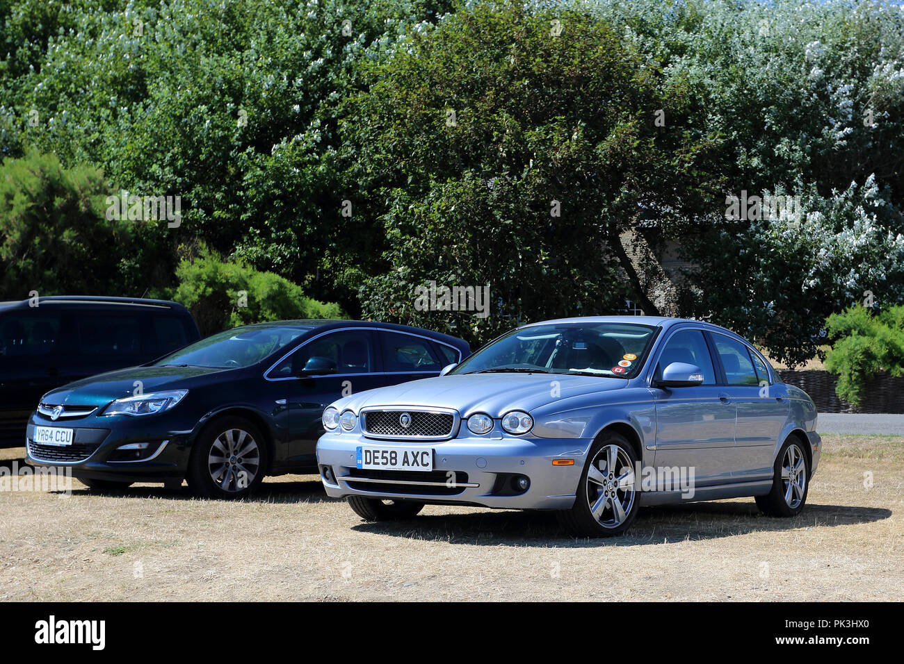 A lilac Jaguar X-Type stands in a car park next to a blue Vauxhall car. - Stock Image