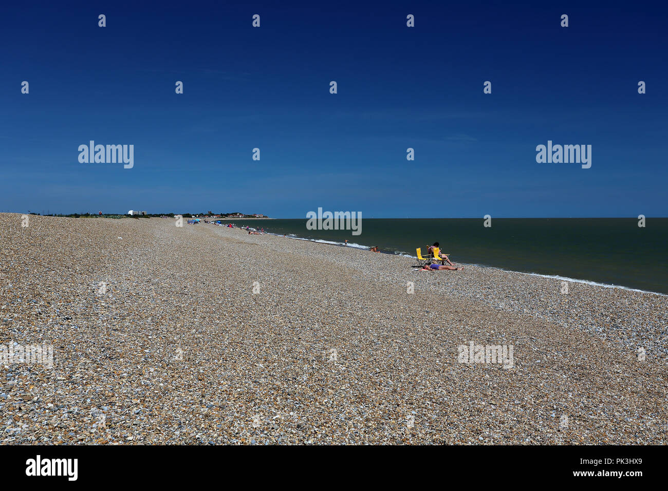 Sunbathing holidaymakers relax on a hot summer's day at the shingle beach at Aldeburgh, Suffolk, UK - Stock Image