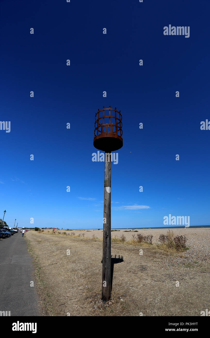 Weeds grow high in the hot summer sun around an old signalling beacon alongside a track next to the shingle beach at Aldeburgh, Suffolk, UK - Stock Image