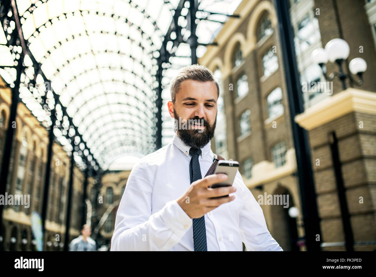 Businessman with smartphone on the trian station in London, text messaging. - Stock Image