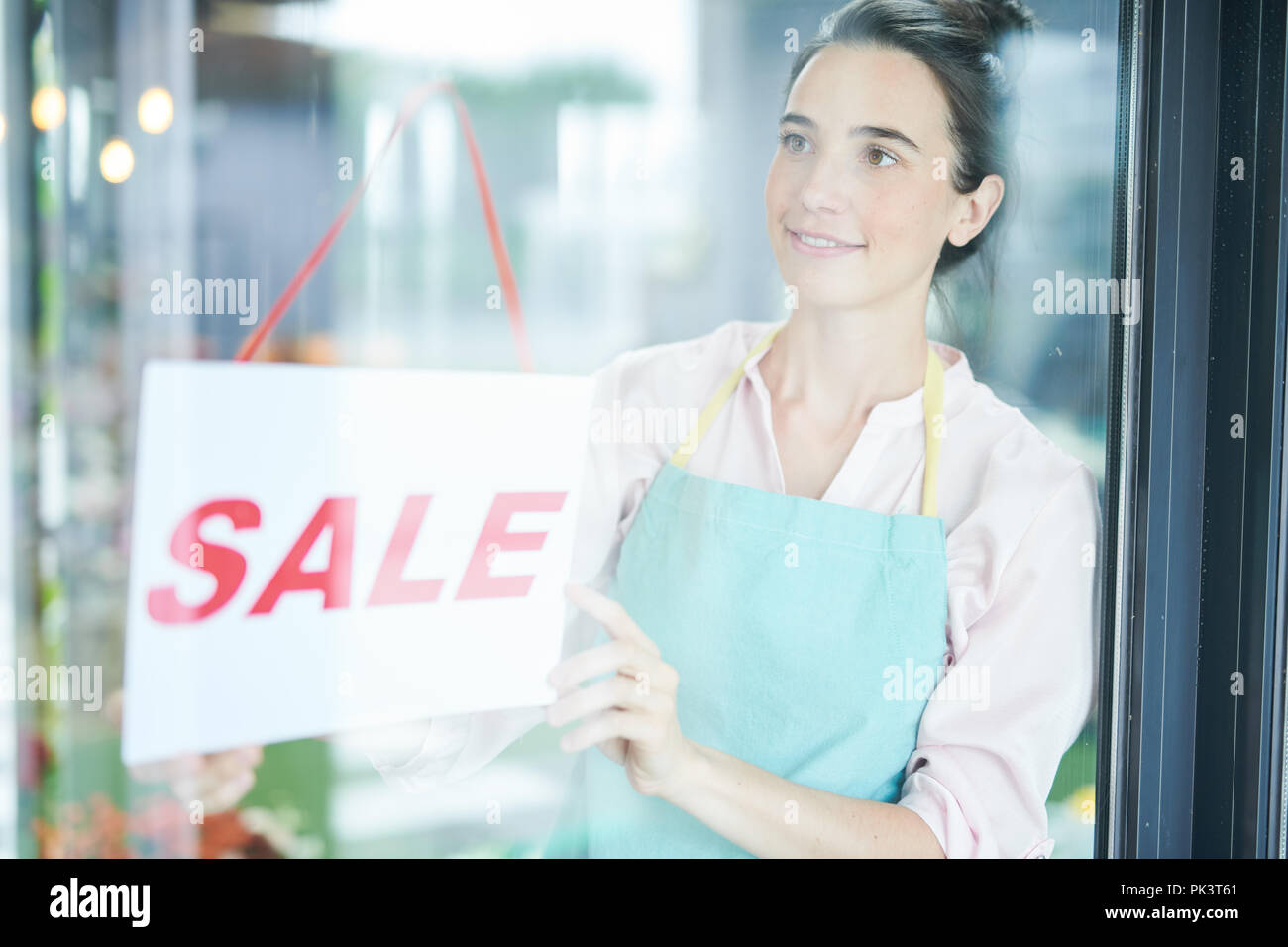 Shopkeeper Hanging SALE Sign - Stock Image
