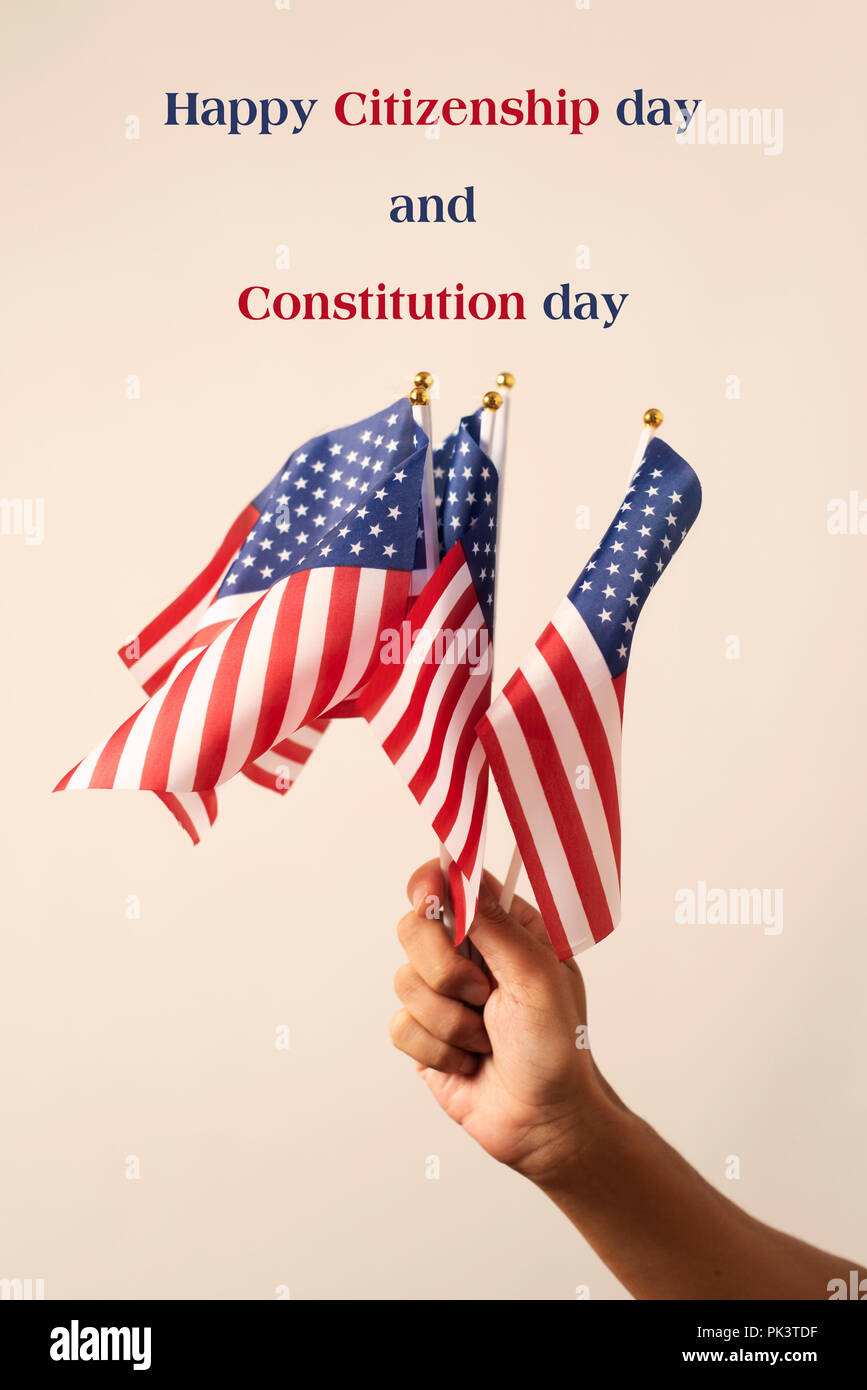 closeup of a man weaving some flags of the United States and the text happy citizenship day and constitution day against an off-white background - Stock Image