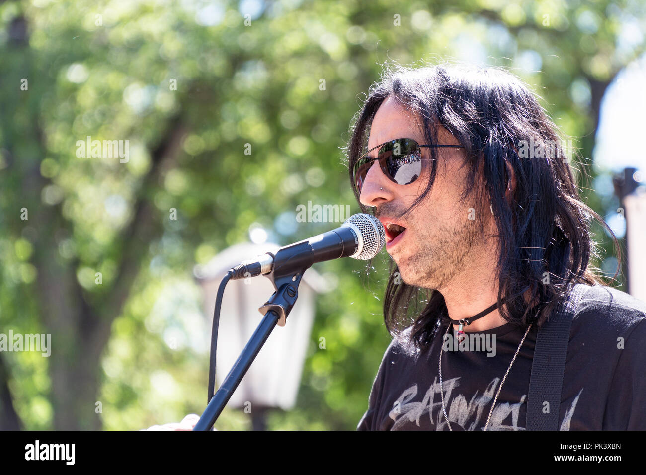 Unknown singer sings into the microphone in the Park - Stock Image