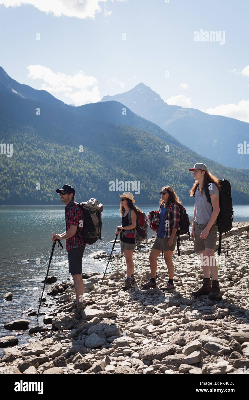 Group of hikers standing near riverside - Stock Image