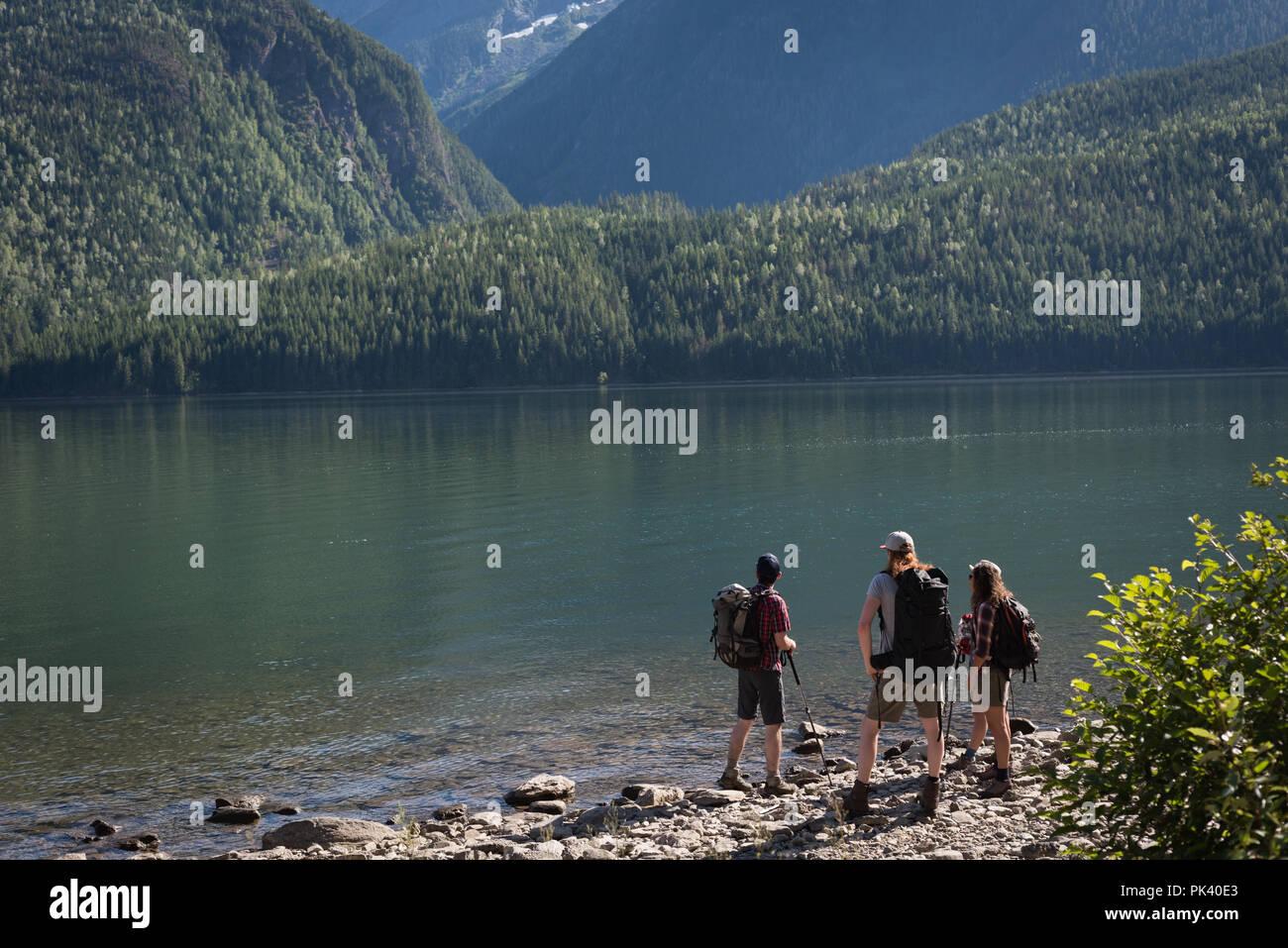 Hikers standing near riverside - Stock Image