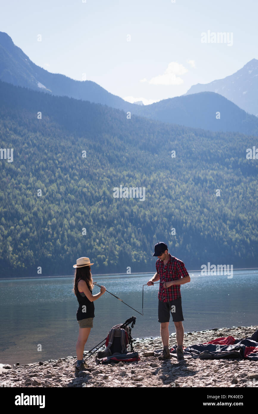 Couple making preparation for setting up a tent - Stock Image