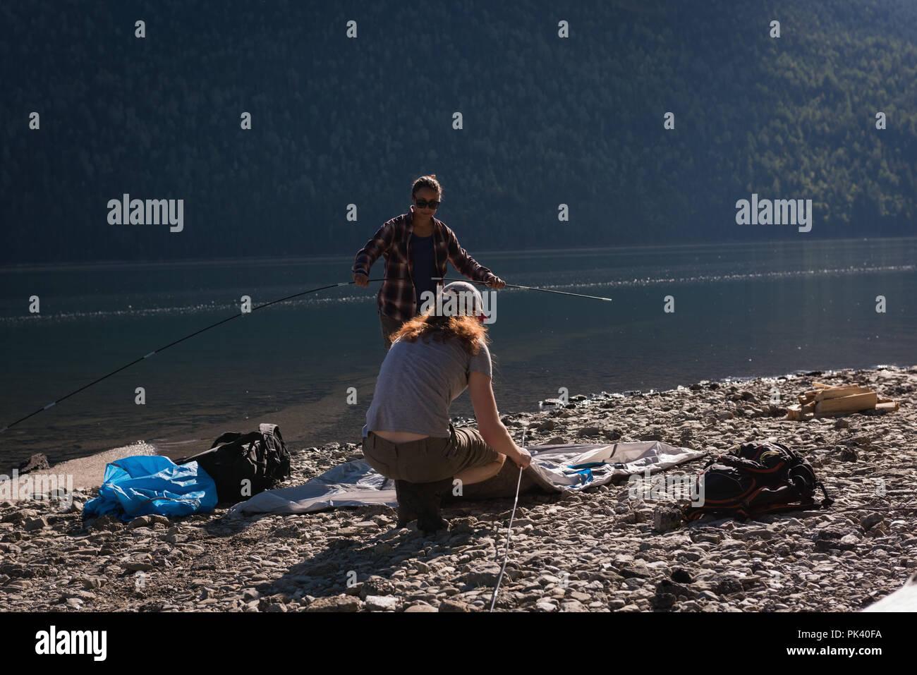 Couple setting up tent near riverside - Stock Image