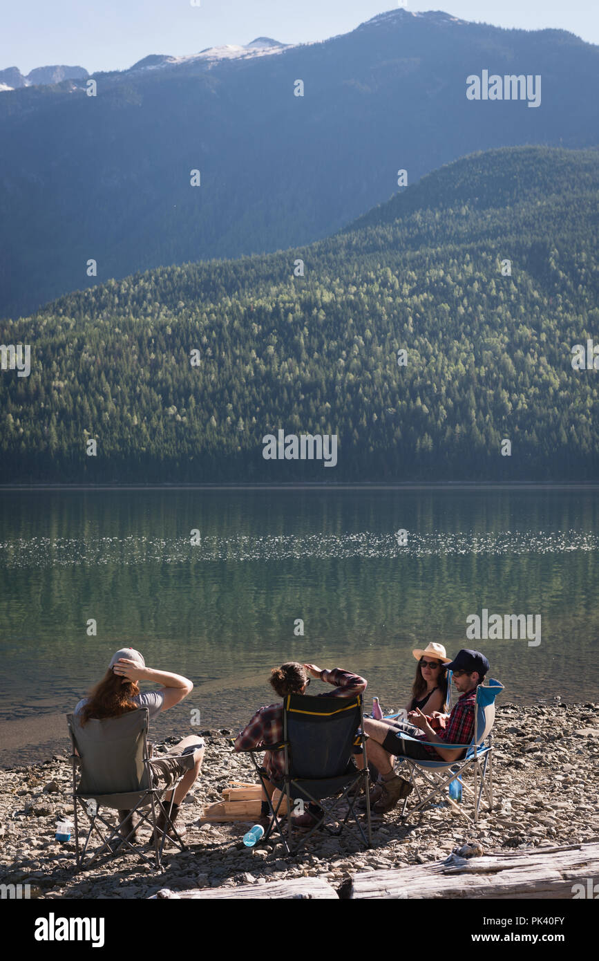 Group of hikers camping near riverside - Stock Image