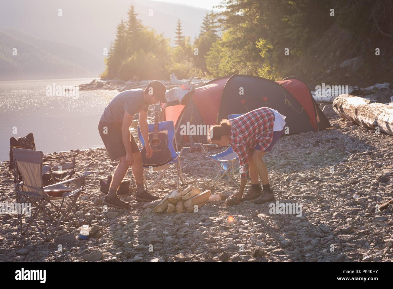 Couple preparing campfire near riverside - Stock Image