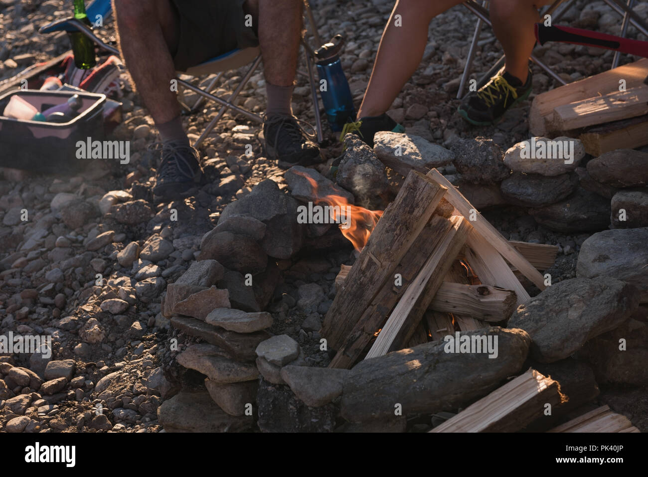 Couple camping near campfire - Stock Image