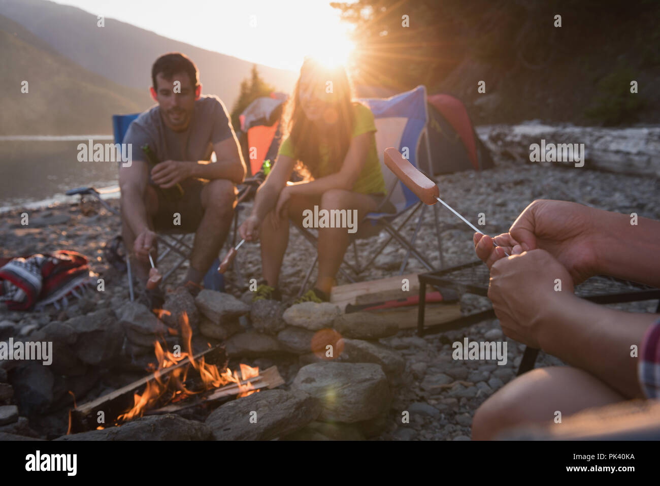 Group of friends heating hot dog near campfire - Stock Image