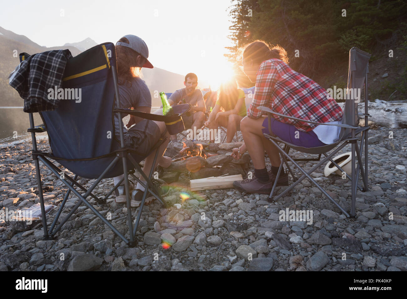Group of friends roasting hot dogs on campfire - Stock Image
