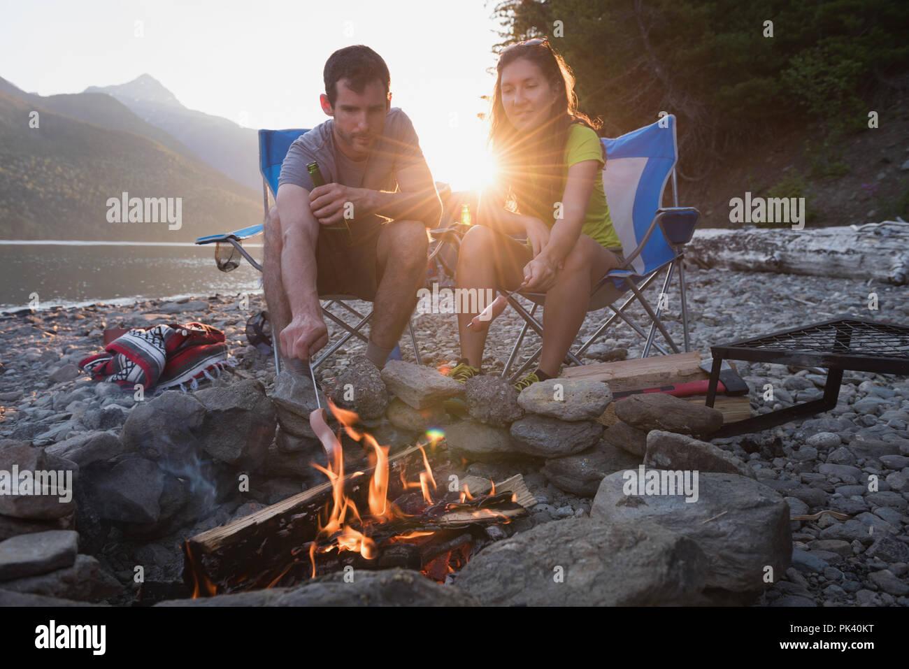 Couple roasting hot dog on campfire - Stock Image