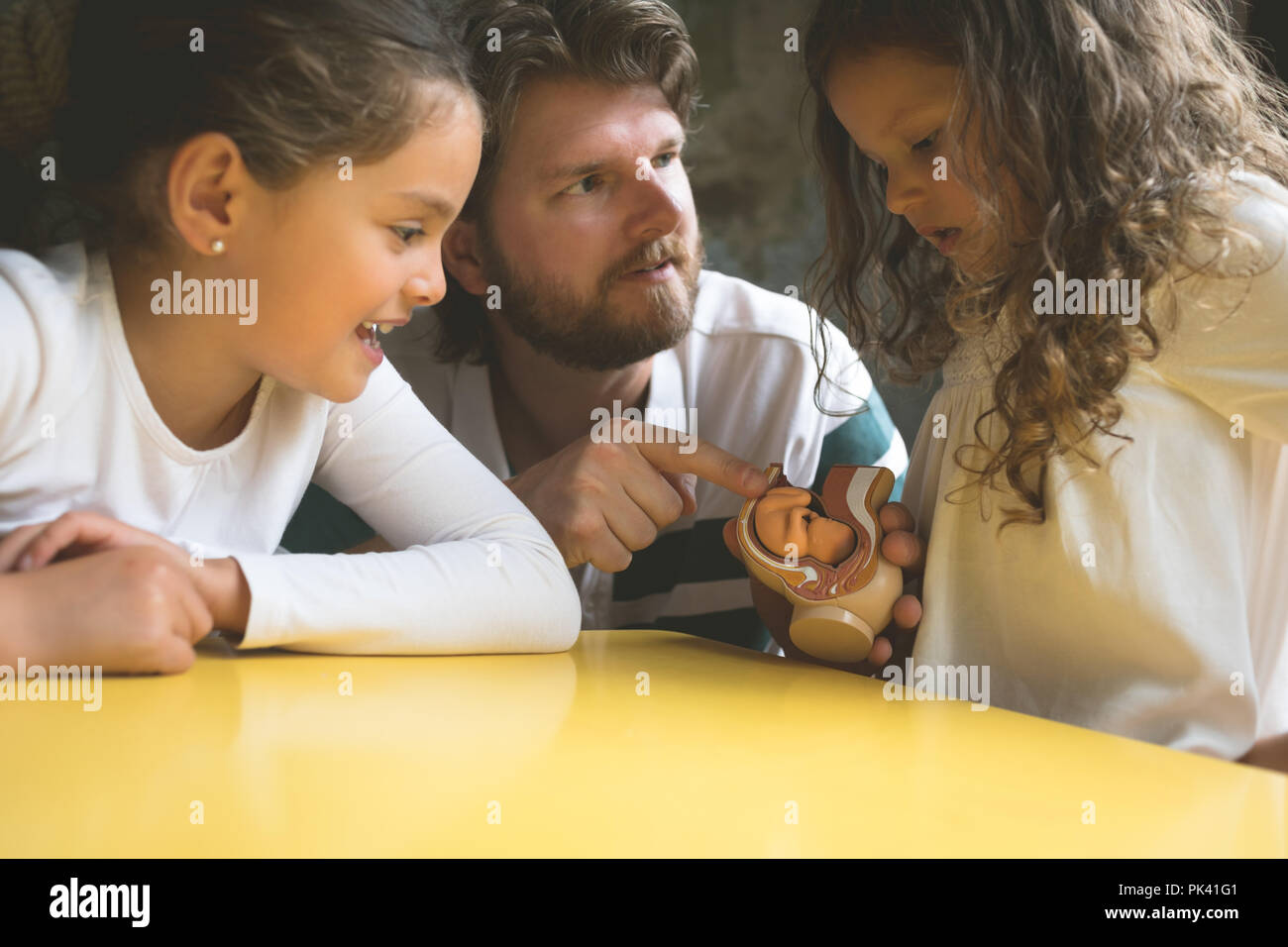 Father explaining his daughters about fetus model - Stock Image