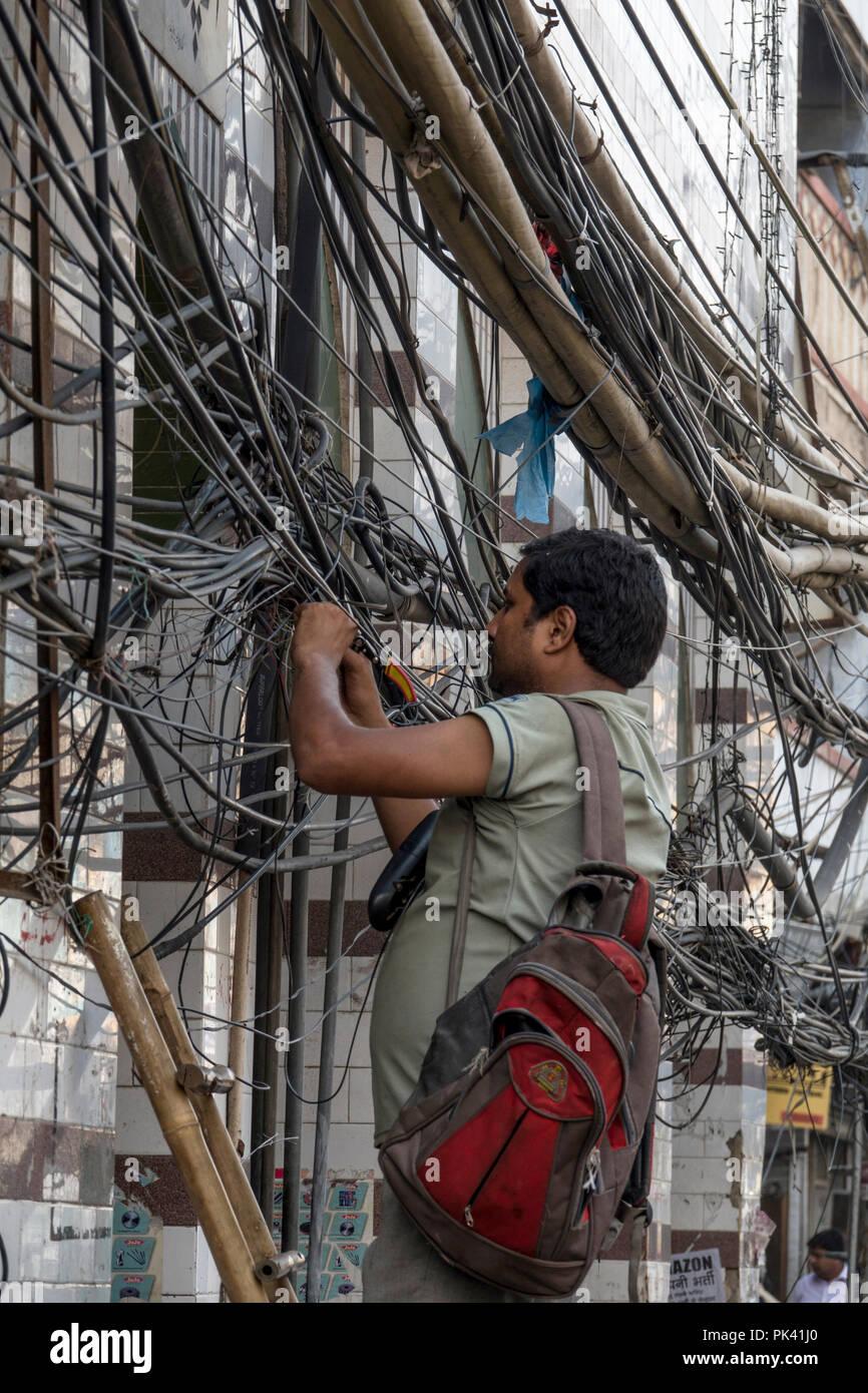 Technician fixing power lines in Old Delhi, New Delhi, Delhi, India - Stock Image