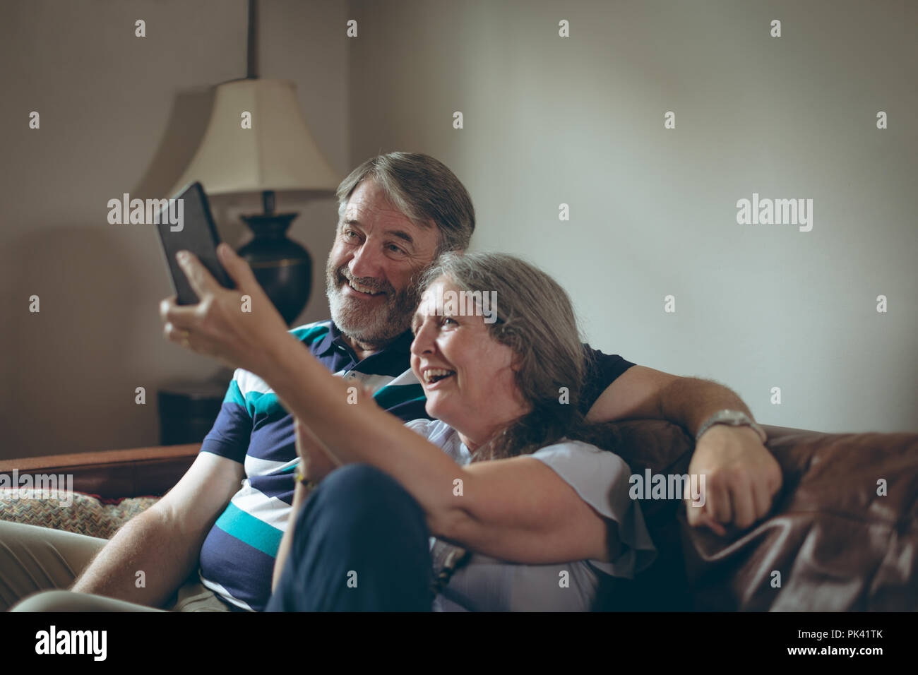 Senior couple taking selfie on mobile phone at home - Stock Image