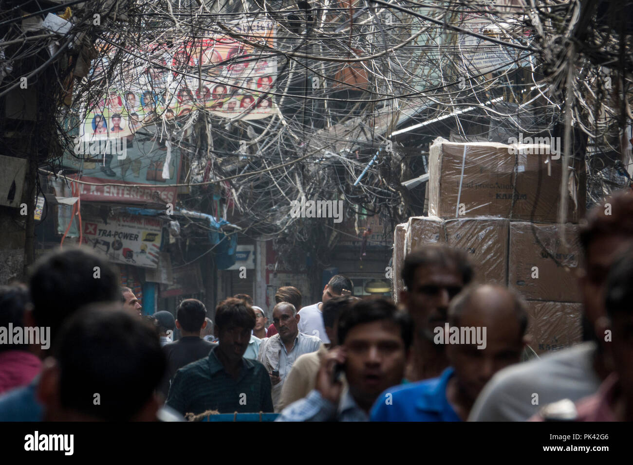 Pedestrians walking in narrow street with large tangled bird's nest of power cables overhead in Old Delhi, New Delhi, Delhi, India - Stock Image