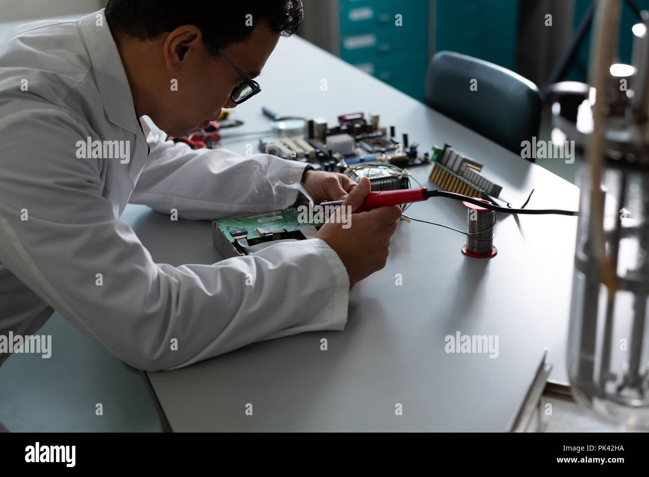 Male scientist experimenting on circuit board - Stock Image