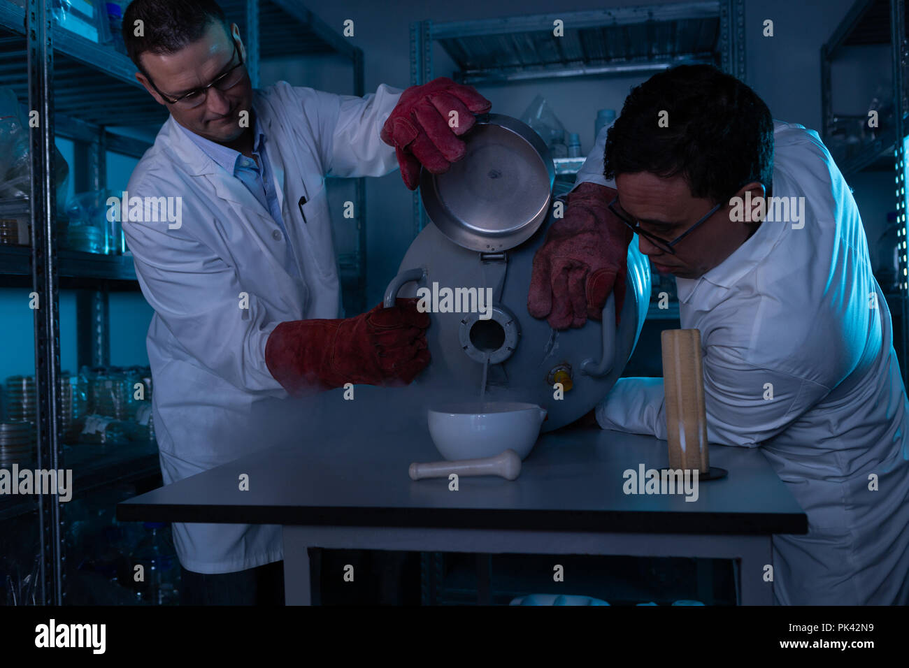Male scientists pouring liquid in a bowl - Stock Image