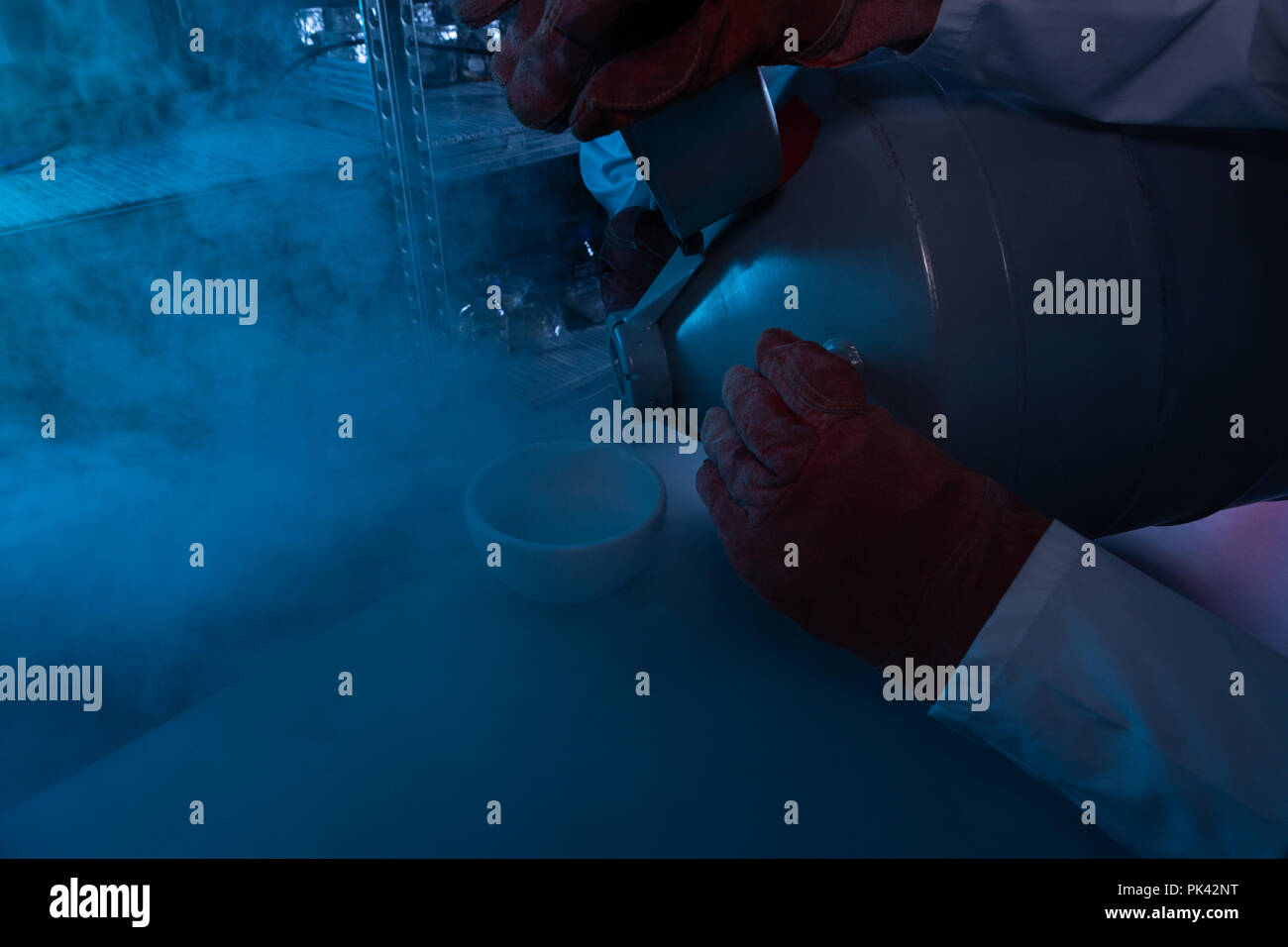 Male scientist pouring liquid in a bowl - Stock Image