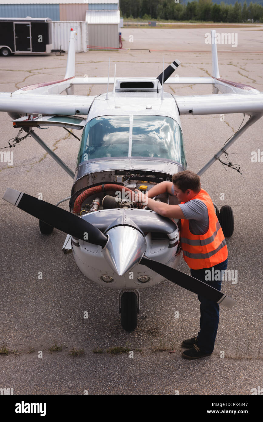 Engineer servicing aircraft engine near hangar - Stock Image