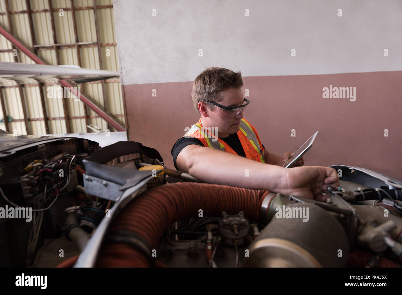 Mechanic using digital tablet while servicing aircraft engine - Stock Image