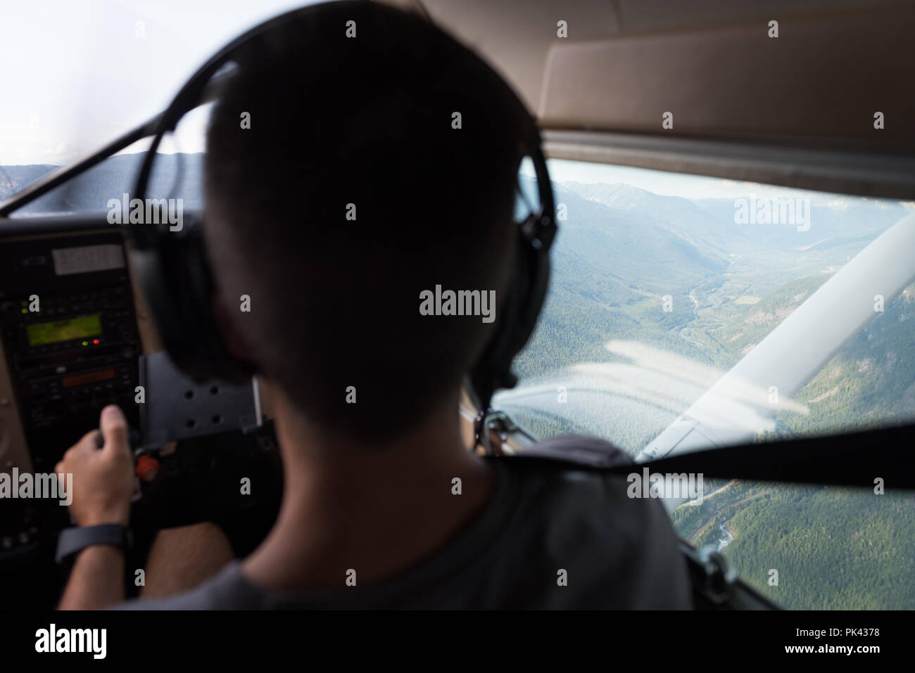 Pilot flying aircraft over mountains and landscape - Stock Image