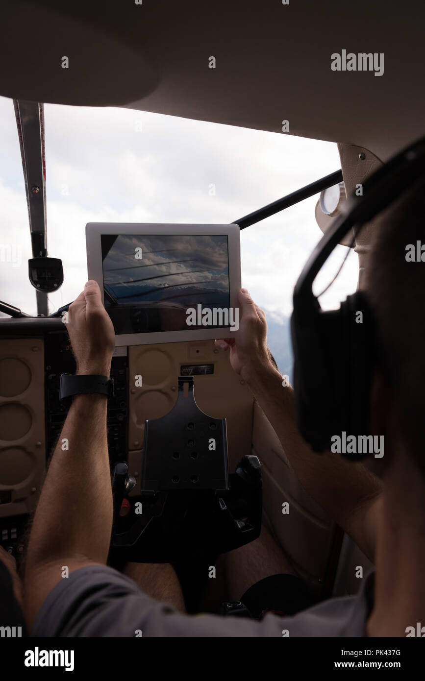 Pilot taking photos with digital table while flying - Stock Image